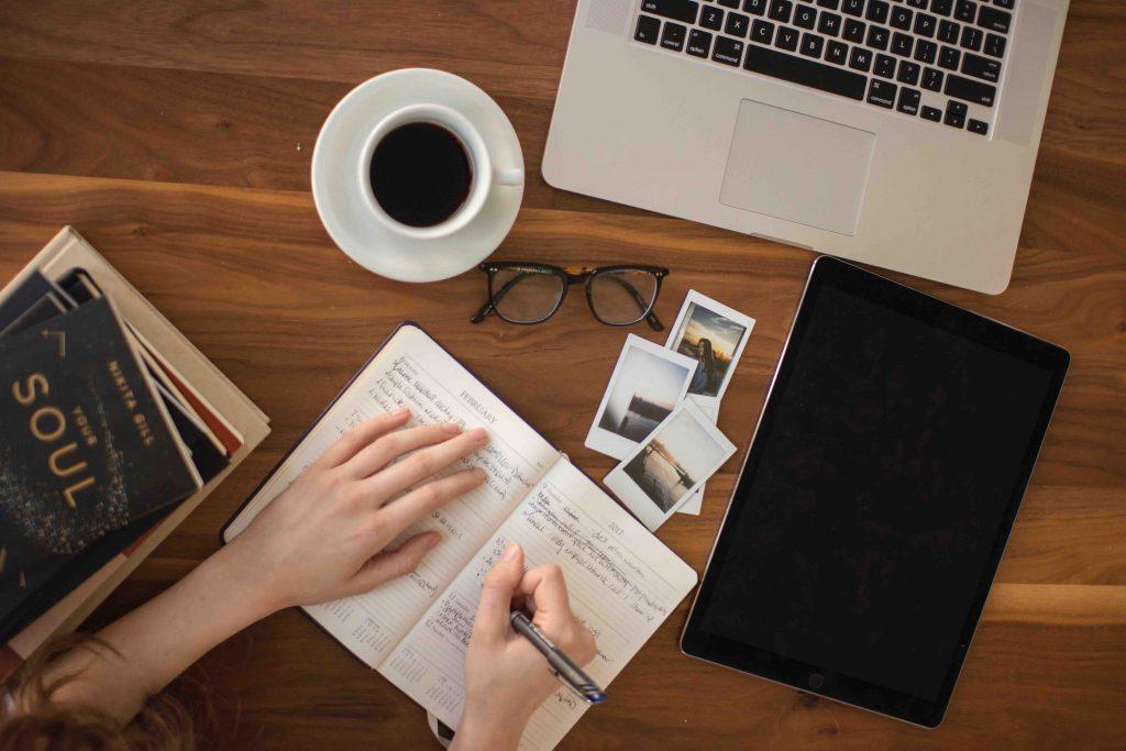 Frau schreibt Ex-zurück Strategie in ihr Notizbuch, das auf einem vollen Schreibtisch mit Laptop, Kaffee, Polaroidbildern, Brille und Büchern liegt.