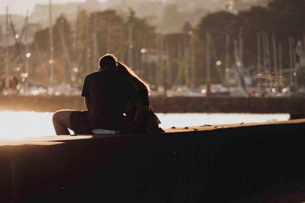 Ex-Freund zurückholen: Paar sitzt kuschelnd bei Sonnenuntergang auf Mauer am Hafen