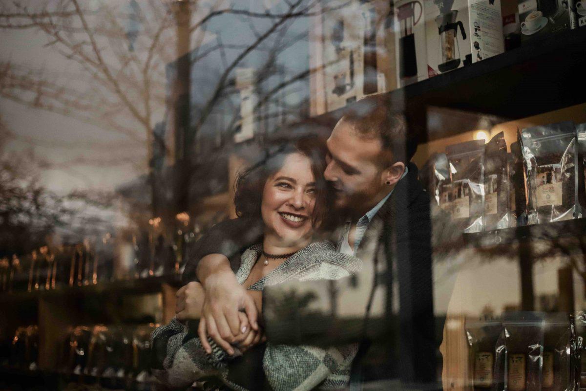 Partner finden und festhalten: Hinter einer Fensterscheibe umarmt sich ein glückliches Paar