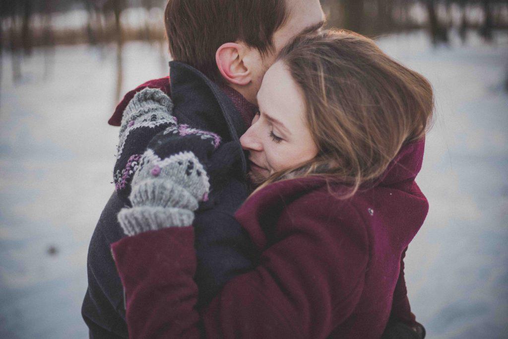 7 Tipps, um deine/n Ex zurückzugewinnen: Paar steht auf schneebedeckter Wiese und umarmt sich innig.